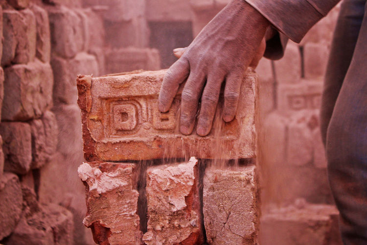 Human hand on stone wall