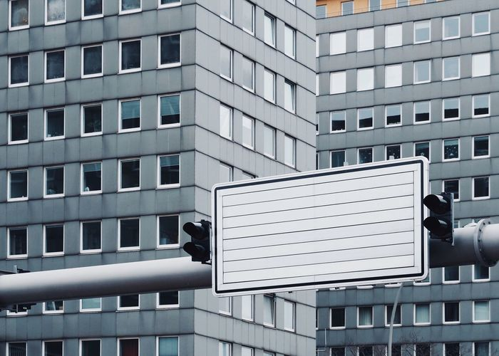 Blank road sign against building