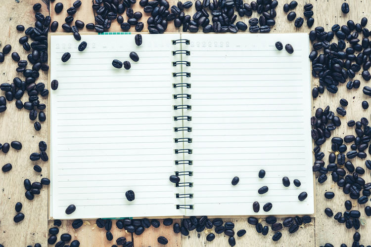 Directly above shot of spiral notebook surrounded with coffee beans on wooden table
