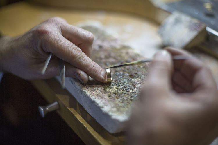 Midsection of person working on a handmade ring