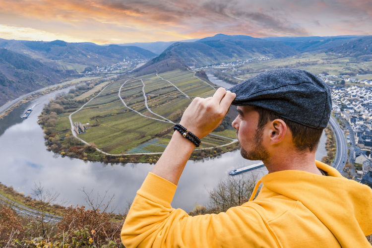 Close-Up Of Man Looking At View On Mountain Against Sky
