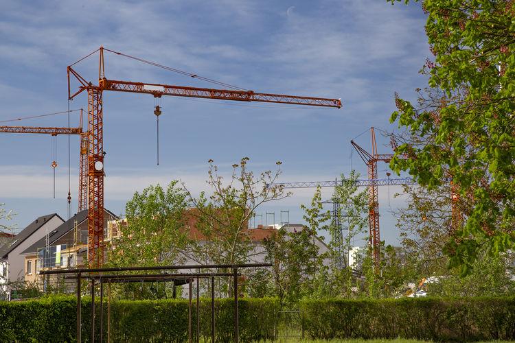 Crane by building against sky