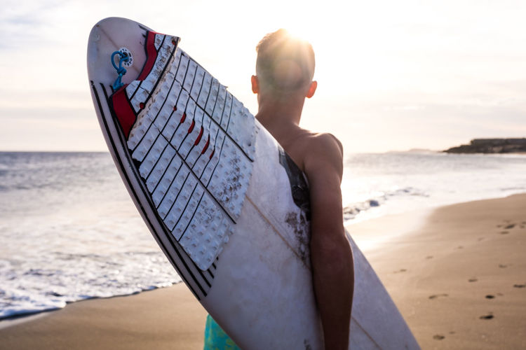 Rear view of boy holding surfboard standing on beach