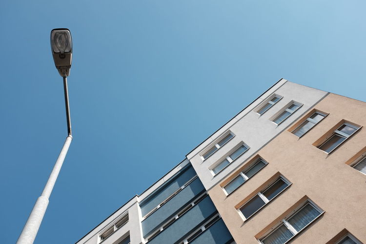Low angle view of street light by building against clear blue sky