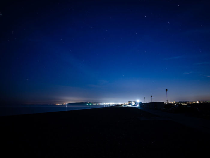 Scenic view of beach against blue sky at night