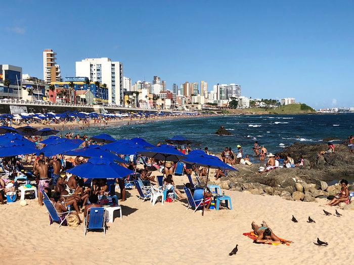 People on beach against clear blue sky