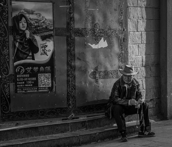 Real People One Person Sitting Seat Leisure Activity Lifestyles Architecture Full Length Casual Clothing Hat Day Built Structure Clothing Looking Away Front View Bench Young Men Men Looking Outdoors Waiting Street Streetphotography Hat Blackandwhite Poster Tibet