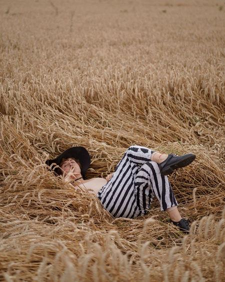 Rear view of man relaxing on field