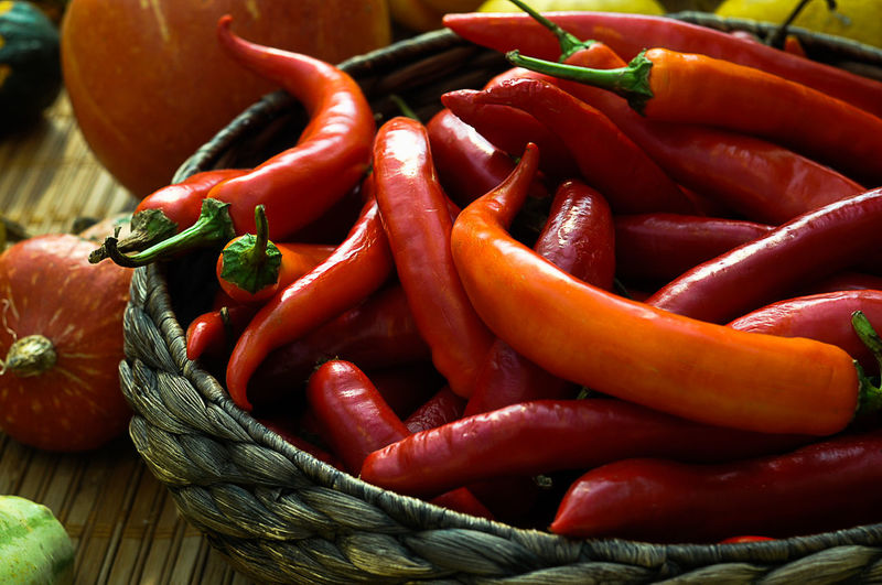 Close-Up Of Red Chili Peppers In Wicker Container On Table