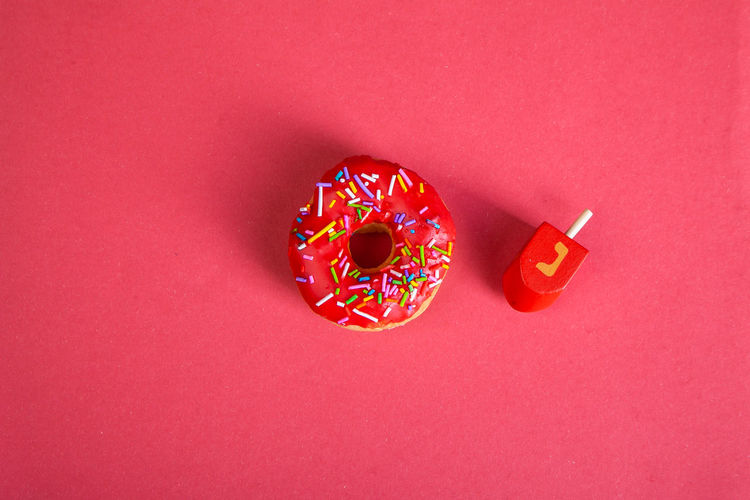 Directly above shot of multi colored candies against red background
