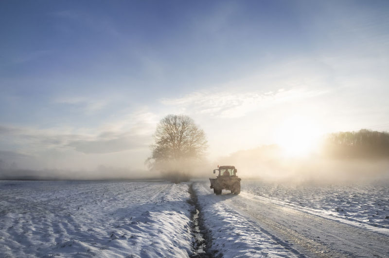 Vehicle on snow covered road against sky during sunset