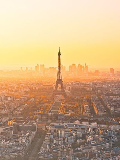 Eiffel tower amidst buildings in city during sunrise