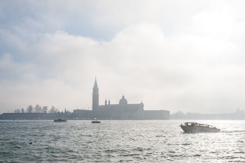 Boat moving on grand canal by san giorgio maggiore against sky