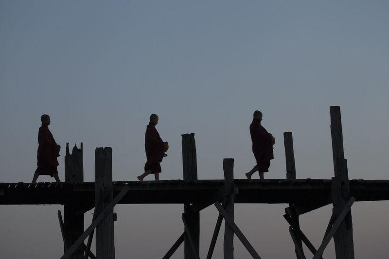 Silhouette monks walking on footbridge against clear sky during sunset
