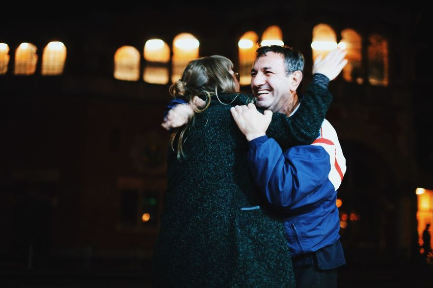 Mature man is hugging young woman Night Togetherness Two People Friendship Diversity Illuminated Nightlife Smiling Real People Focus On Foreground Bonding Fun Happiness Enjoyment Embracing Leisure Activity Standing Lifestyles