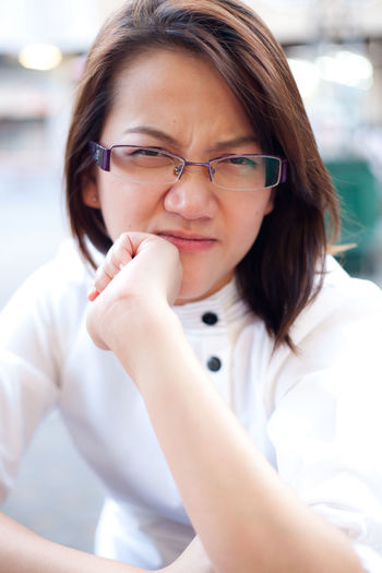 Close-Up Portrait Of Young Woman Wearing Eyeglasses Outdoors