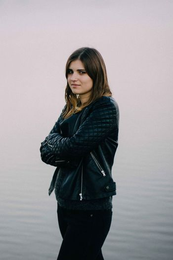 Young Woman Wearing Black Jacket While Standing Against Lake