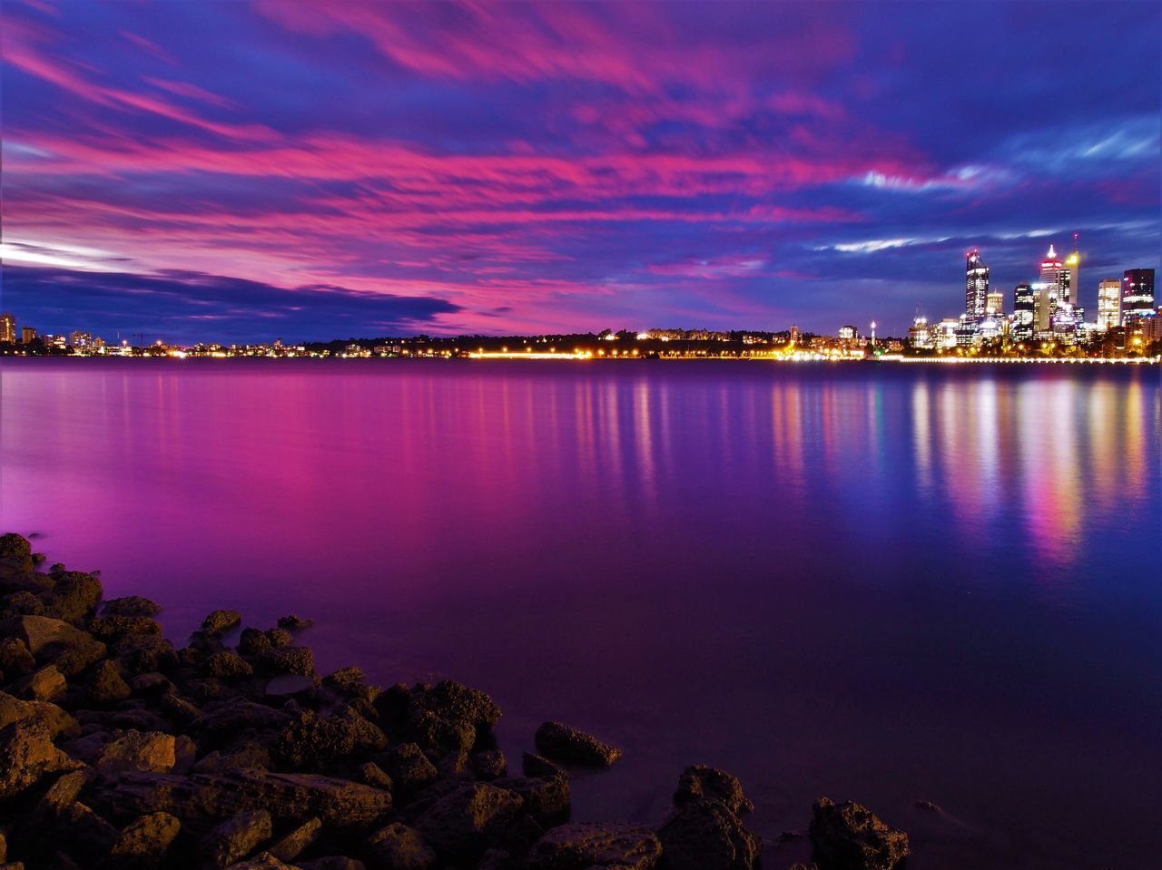 Scenic View Of Lake And Illuminated City Against Sky At Dusk
