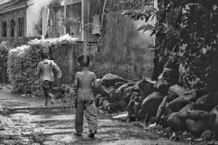 Rear view of people walking by buildings in city