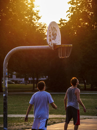 URBANANA #urbanana: The Urban Playground Basketball Available Light Ball Basketball - Ball Basketball Hoop Boys Leisure Activity Lifestyles Males  Men Nature Outdoors People Plant Real People Rear View Sky Sport Streetphotography Sunset Togetherness Tree Two People urban sports