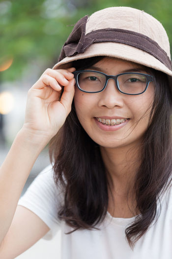 Close-up portrait of smiling young woman wearing hat