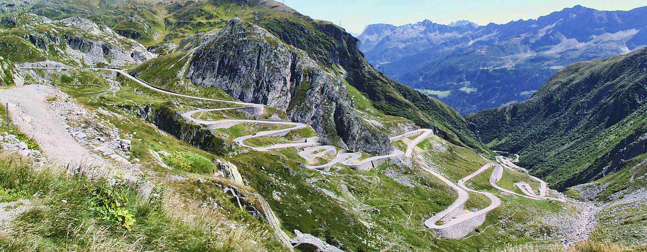 mountain, nature, high angle view, winding road, scenics, beauty in nature, tranquility, mountain range, tranquil scene, road, day, mountain road, outdoors, the way forward, curve, no people, landscape, grass, sky