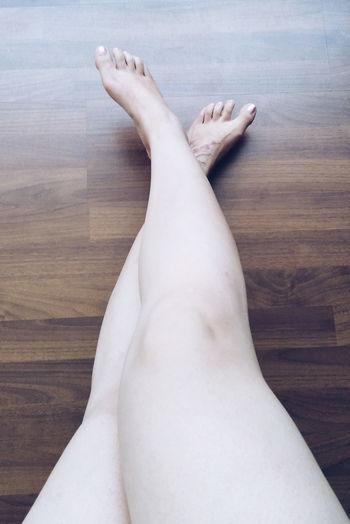 Low section of woman lying on hardwood floor