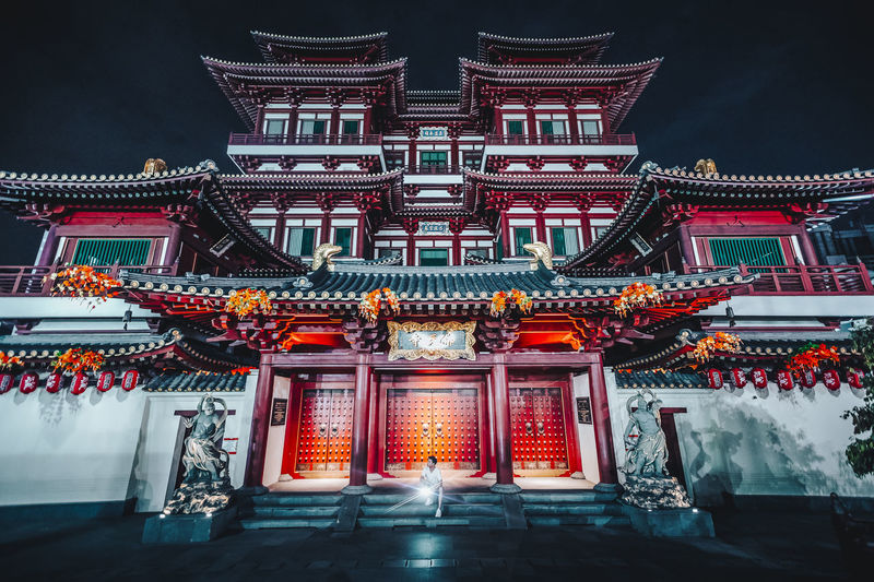 Man sitting against buddhist temple at night