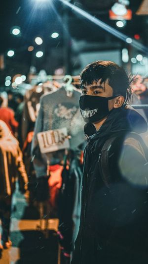 Man wearing mask and looking away while standing in store