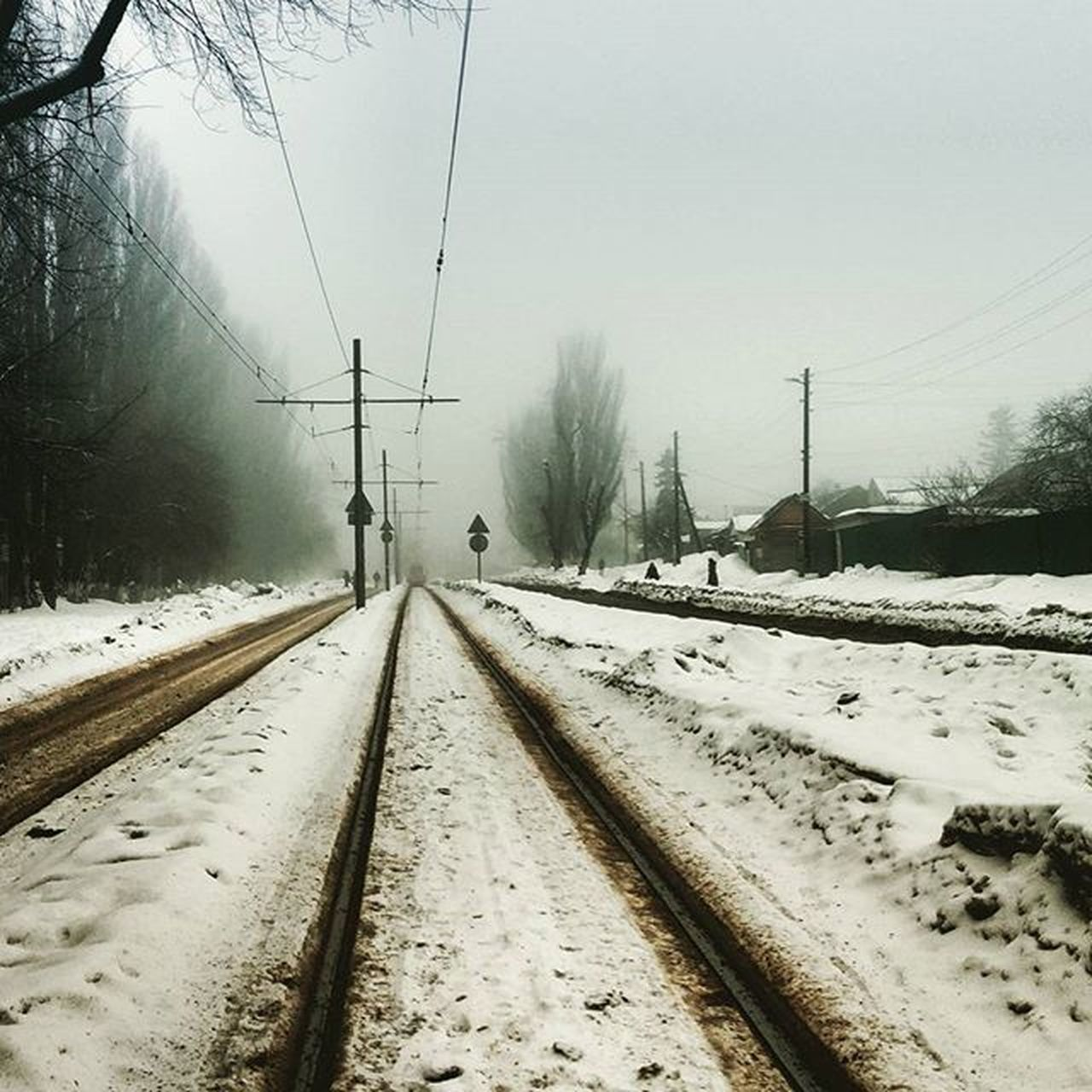 snow, cold temperature, winter, transportation, rail transportation, track, railroad track, tree, cable, covering, nature, sky, direction, electricity, the way forward, mode of transportation, no people, white color, land, diminishing perspective, outdoors, snowcapped mountain