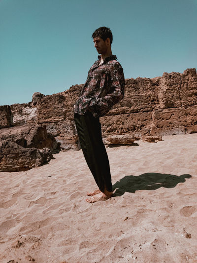 Young man standing on rock against clear sky