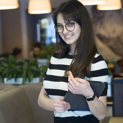Shot of a young woman working in a restaurant Happy Small Business Woman Working Adorable Anticipation Beautiful Woman Beauty Caucsian Cheerful Day Eyeglasses  Eyeglasses  Focus On Foreground Front View Happiness Indoors  Lifestyles Long Hair Looking At Camera Manager Medium-length Hair Portrait Pretty Real People Restaurant Shot Smile Smiling Standing Three Quarter Length Waiter Women Young Adult Young Women
