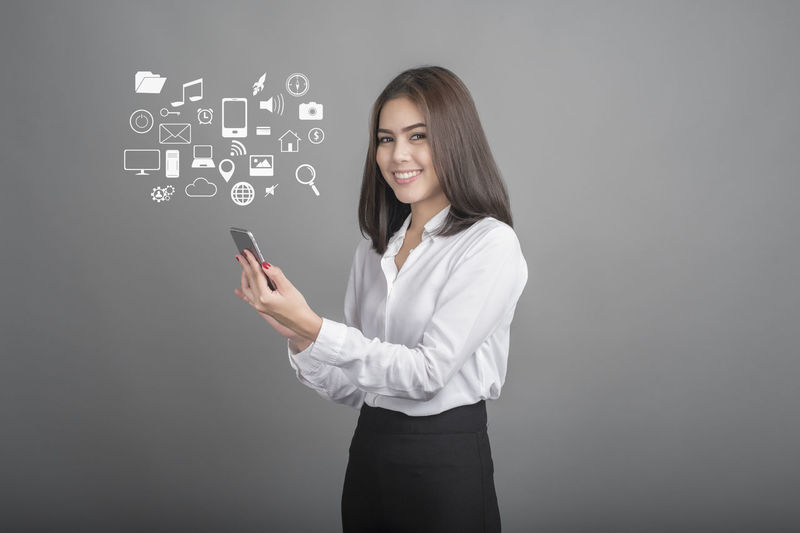 Adult Blackboard  Business Business Businesswoman Chats Communication Connection Finance Global Communications Globalization Indoors  Internet Looking At Camera One Person One Woman Only Only Women Portrait Smart Phone Smiling Standing Talking Photo Tech Technology Young Adult