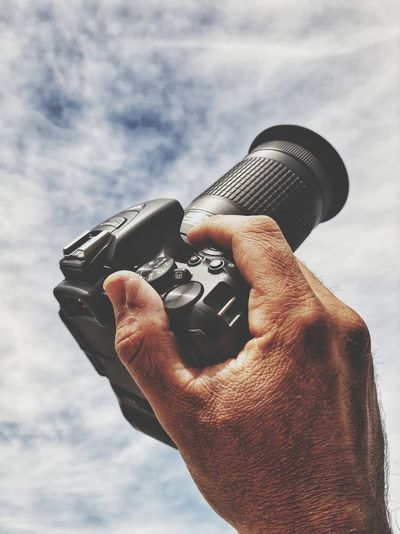 Close-up of man holding camera against sky