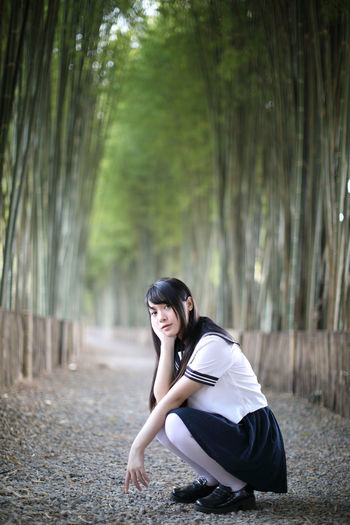 Portrait of young woman crouching amidst bamboo groove