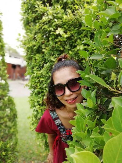 Portrait of smiling woman wearing sunglasses standing amidst plants in park