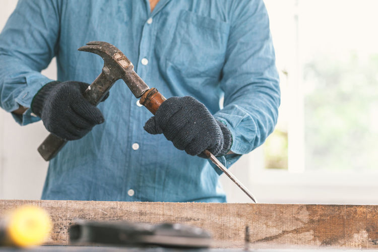 Low angle view of man working on wood