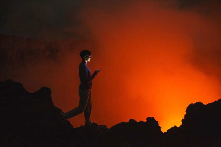 Woman Looking At Volcanic Eruption