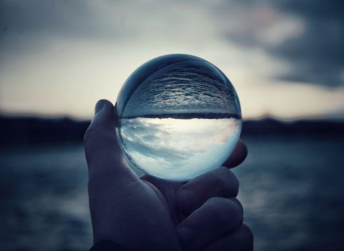 Man holding crystal ball during dusk