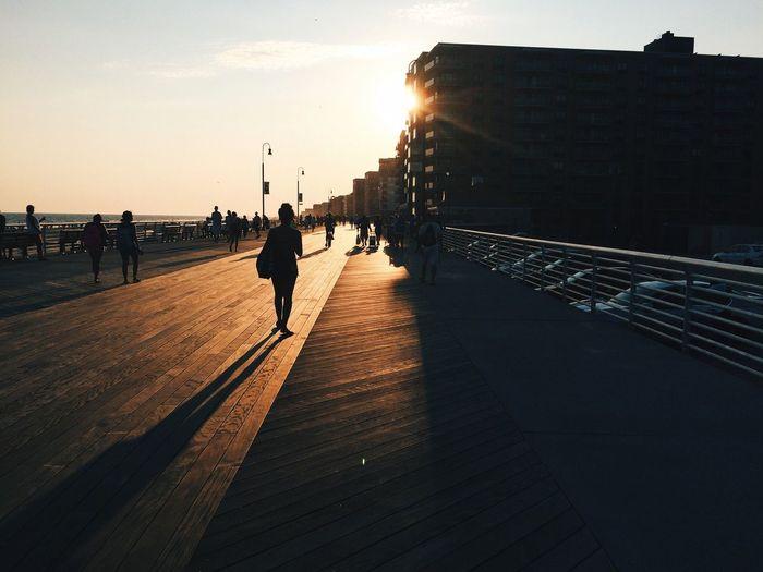 Silhouette people walking on bridge in city during sunset