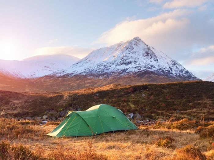 Green touristic tent on meadow at river below snowy cone of stob dearg 1021 metres high. hikers tent