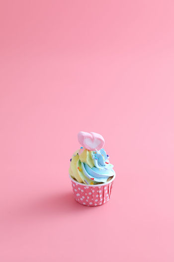 High angle view of cupcakes against pink background