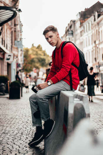 Young man riding motorcycle on street in city