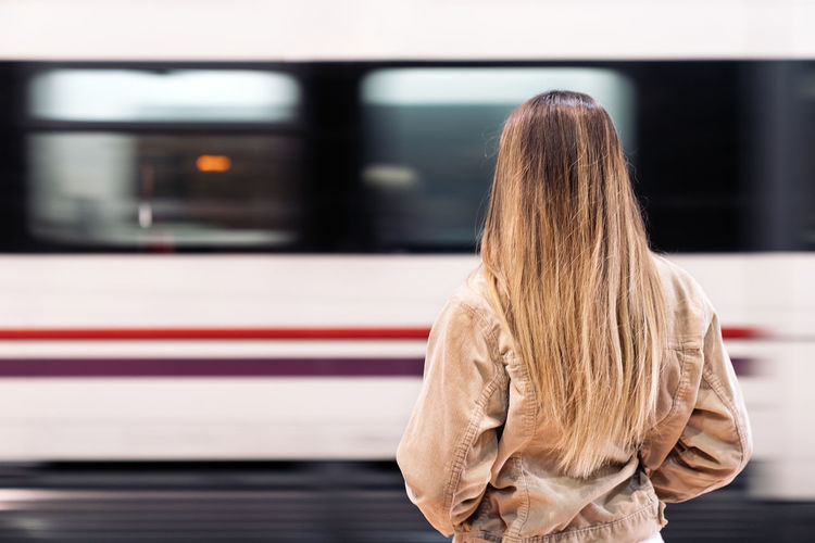 Rear view of woman looking at train