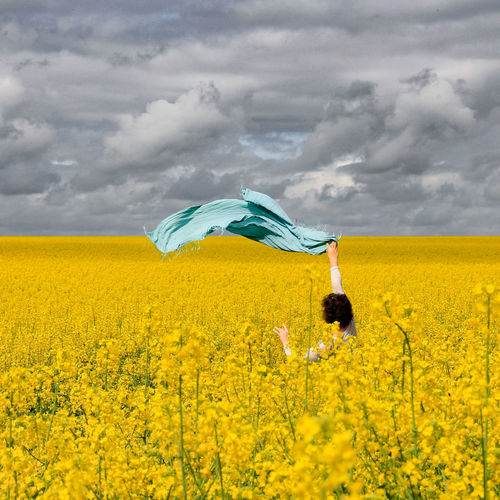 Woman holding scarf at oilseed rape field