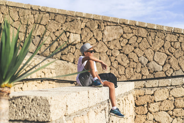 Full length of boy sitting by stone wall