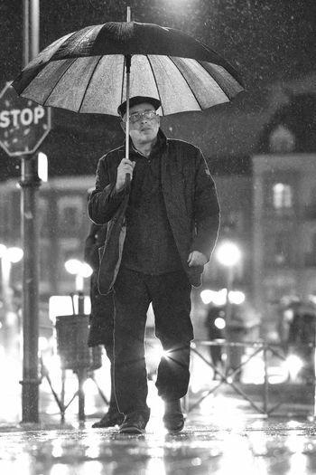 Full length portrait of man standing on wet rainy day