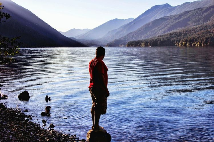 Side view of man standing on rock by lake against mountains