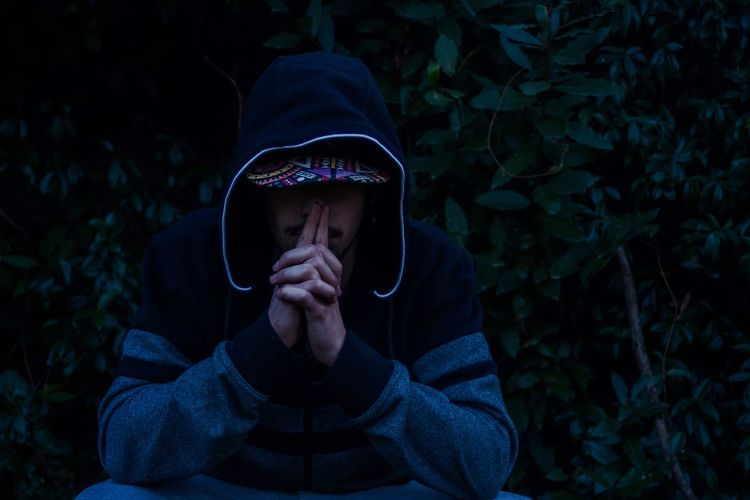 Worried man in hood clothing sitting at forest