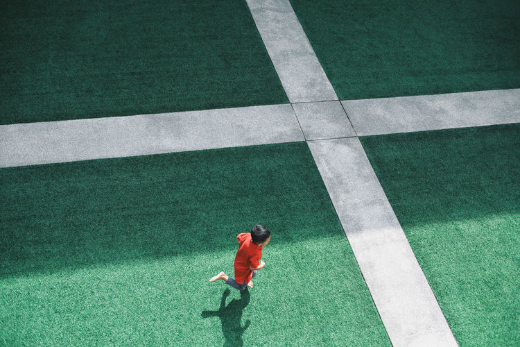 Cross EyeEm Ready   Green Artificial Grass Boy Running Courtyard  Grass Green Color High Angle View Lifestyles Playing Red Red Shirt Sports Track Fresh On Market 2018 17.62°
